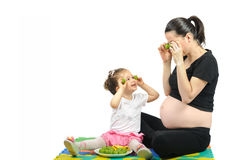 Isolated first child playing to her pregnant mother with fruits on white Stock Images