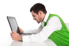 Isolated frustrated businessman with laptop at desk on white. Royalty Free Stock Photo
