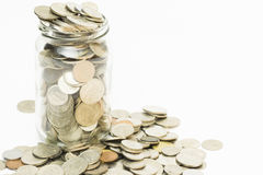 Isolated full of coins in jar and spill out Stock Photos