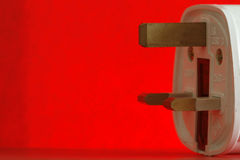 Isolated fuse. An  electricity fuse adaptor in a simple red background Royalty Free Stock Image