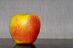 Isolated Gala Apple on a table. With a grey fabric background royalty free stock photography