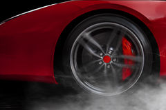 Isolated generic red sport car with detail on wheel with red breaks drifting and smoking on a dark background Royalty Free Stock Photo