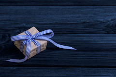 Isolated gift box with blue strips on wooden background. Royalty Free Stock Images