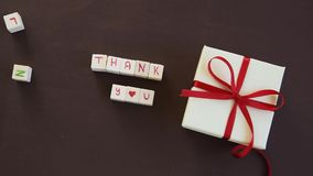 Isolated gift box with `Thank you` on text. Isolated gift box with `Thank you` text on brown background stock video footage