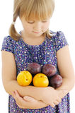 Isolated girl holding plums. Calm girl looking at the plums in her crossed hands on the white isolated background stock photo