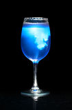 Isolated glass with blue splashing beverage Royalty Free Stock Photos