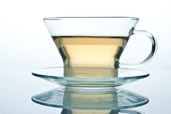 Isolated glass cup of tea or another liquid. With reflection standing on a glass table Stock Photos