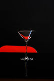 An isolated glass for martini on dark and red background. Cocktail.  Royalty Free Stock Images