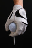 Isolated golf ball, gloved hand and tee. Closeup of golfers gloved hand, golf  ball and golf tee against a black background Stock Photos