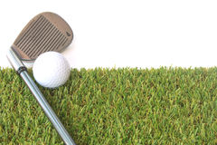 Isolated golf ball on green grass over white background Stock Images