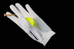 Isolated golf glove with ball and tee, on black. Royalty Free Stock Image