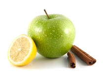 Isolated green apple and lemon with cinnamon pods. Isolated wet green apple and lemon with cinnamon pods (white background). Fresh diet fruit (water drops) Royalty Free Stock Image