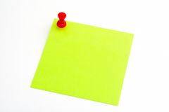 Isolated green paper with red pushnail stock image