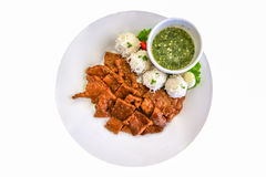 Isolated grilled pork with rice noodle in the white plate with chilli dipping sauce Royalty Free Stock Photo