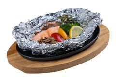 Isolated Grilled Salmon in a Foil Pack with broccoli, bell pepper, mushroom and slice lemon served in hot plate on wooden plate.  Royalty Free Stock Photos