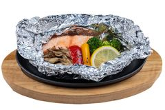 Isolated Grilled Salmon in a Foil Pack with broccoli, bell pepper, mushroom and slice lemon served in hot plate on wooden plate.  Royalty Free Stock Photography
