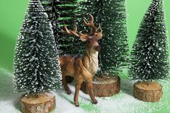 Snowy forest firs and reindeer green Stock Images