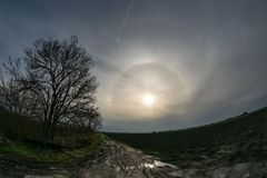 A bright 22 degree halo with upper tangent arc and parhelia over the dutch countryside stock images