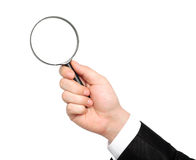 Isolated hand of a businessman in suit holding a magnifying glas Royalty Free Stock Image