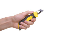 Isolated hand holding cutting knife tool. Isolated hand holding yellow construction knife tool Stock Images