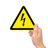 Isolated hand holding sign of danger high voltage. Isolated male hand holding yellow sign of danger high voltage symbol with lightning Stock Images