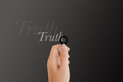 Isolated hand with lens and text truth on dark platinum backgrou Stock Photo