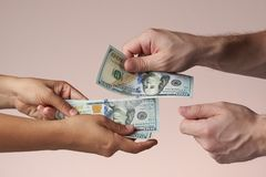Hands exchanging money. Isolated hands exchanging money. Holding dollars in hands. Giving money concept stock image