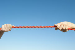 Isolated Hands pulling rope. Two hands gripped around orange rope and pulling in contest, isolated with blue sky as background and copy space stock photo