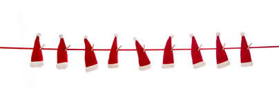 Isolated hanging red santa hats over white background. Royalty Free Stock Images