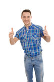 Isolated happy young man in blue with thumbs up. Royalty Free Stock Photo