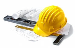 Isolated hard hat with blueprints and rulers. Hard hat with blueprints and rulers on white royalty free stock image