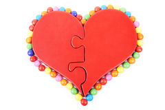 Isolated heart puzzle with sweets around it Royalty Free Stock Photo