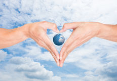 Isolated heart shape hands and the world Royalty Free Stock Images
