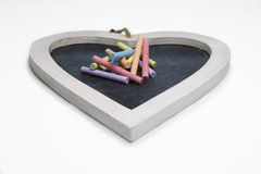 Isolated heart shaped blackboard with colored chalk Stock Images