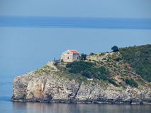 Isolated house to the extremity of a rock in the immensity of the sea. Montenegro royalty free stock image