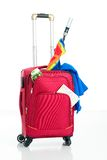 Holiday's luggage. Isolated image of a crammed red suitcase Stock Photo