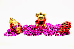 Isolated image. new Year decoration. Golden owl, red pine cone and a golden bear against the backdrop of pink garlands of beads Stock Photography