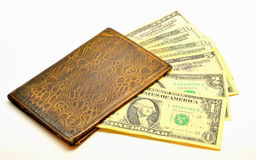 Isolated image. Shabby wallet with dollars. Old, worn leather wallet with dollars lying underneath banknotes of 1, 2, 5, 20 and 100 Royalty Free Stock Photos