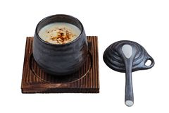 Isolated Japanese custard pudding torched caramel on top served in black ceramic cup on wooden plate with lid and spoon Stock Photo