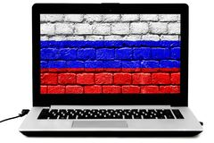 Isolated laptop with the Russian flag painted on a brick wall on the screen. Personal laptop with the Russian flag painted on a brick wall on the screen isoalted stock photo