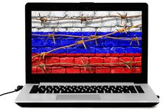 Isolated laptop with rusty barbed wire and Russian flag painted on a brick wall on the screen. Personal laptop with barbed wires and Russian flag painted on a stock photography