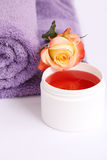 Isolated lilac towel with yellow rose and bath cream Stock Photos