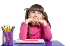 Isolated little girl is sitting at the table with colored pencil Stock Photography