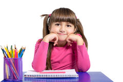 Isolated little girl is sitting at the table with colored pencil stock photo
