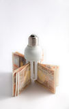 Isolated low consume lamp. With 50 euro banknotes on white background Stock Image