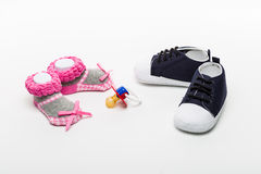 Isolated male and female baby shoes with pacifier at the middle Stock Images