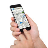 Isolated male hands holding phone with world news site Royalty Free Stock Images