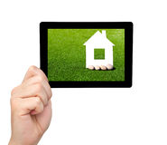 Isolated man hand holding a tablet with grass and a house on the Stock Image