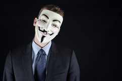 Isolated man wearing Vendetta mask. Man in suit with Vendetta mask Royalty Free Stock Photo