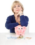 Isolated mature woman with piggy bank Royalty Free Stock Photos